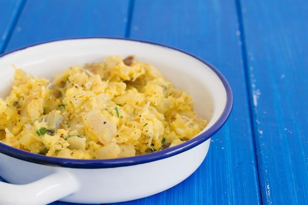 Merluzzo con l'uovo e le erbe sul piatto bianco