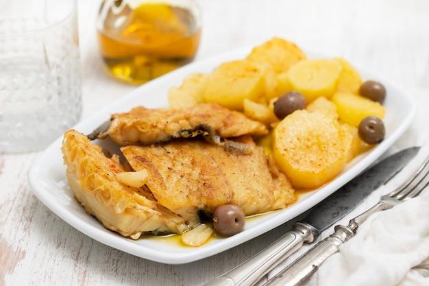 Merluzzo con la patata fritta sul piatto bianco