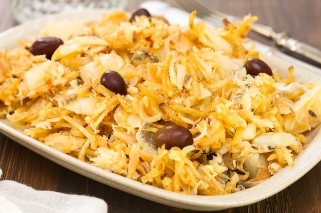Merluzzo con le patatine fritte e le olive sul piatto bianco