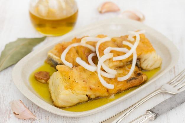 Merluzzo fritto con cipolla e olio d'oliva sul piatto