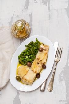Merluzzo fritto con i piselli e i fagiolini sul piatto bianco