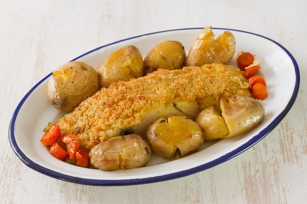 Merluzzo fritto con pane e la patata sul piatto su superficie di legno bianca