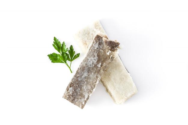 Merluzzo secco salato isolato su superficie bianca alimento tipico di pasqua