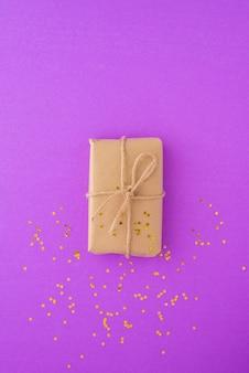 Merry christmas card con confezione regalo avvolto in carta kraft legata con nastro a pois