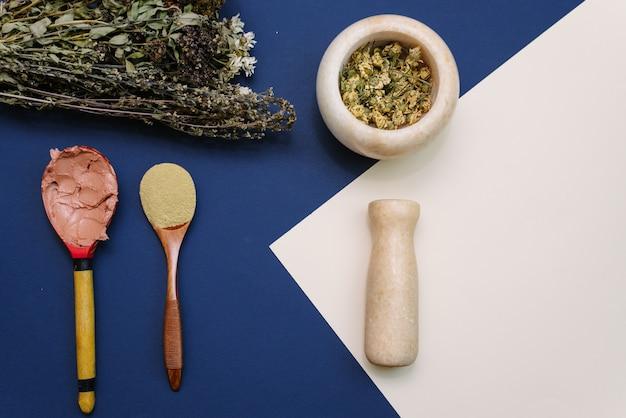 Mescolando i fiori secchi in un mortaio di marmo per creare cosmetici e scrub per pulire il viso. argilla gialla per migliorare le condizioni della pelle in un cucchiaio di legno. bouquet di fiori secchi