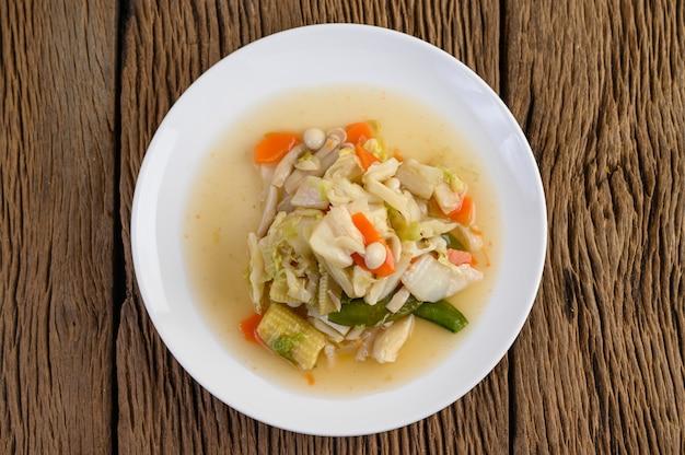 Mescolare friggere le verdure miste su un piatto bianco su un tavolo di legno.