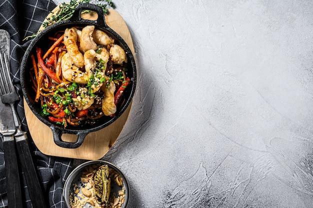 Mescolare gli spaghetti fritti con verdure, pollo. wok noodles. sfondo grigio. vista dall'alto. copia spazio