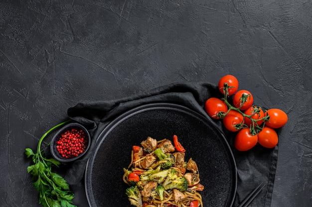 Mescolare gli spaghetti fritti, wok cinese tradizionale. bacchette, ingredienti.