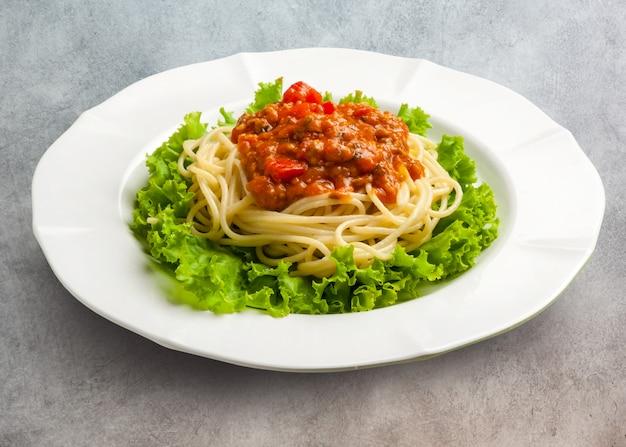 Mescolare gli spaghetti piccanti fritti con carne di maiale e basilico tritati