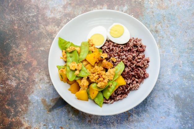 Mescolare i piselli fritti con zucca e pollo, serviti con riso integrale e uovo sodo