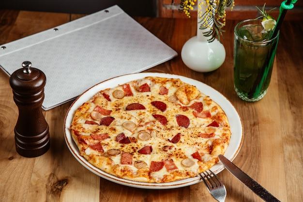 Mescolare i salumi della pizza e la vista laterale del formaggio