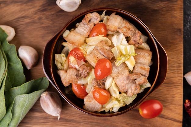 Mescolare il cavolo con la pancetta di maiale in un piatto su un piatto di legno.