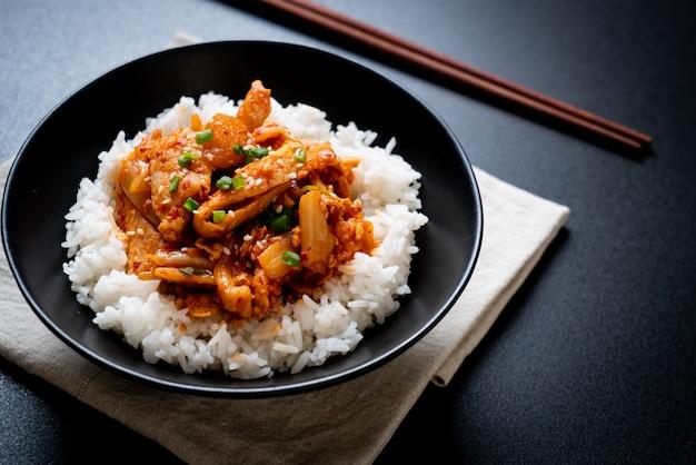 Mescolare il maiale fritto con il kimchi su riso sormontato