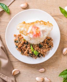 Mescolare la carne di maiale fritta con basilico su riso e uovo fritto