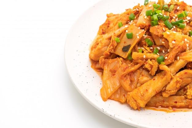 Mescolare la carne di maiale fritta con il kimchi isolato su bianco