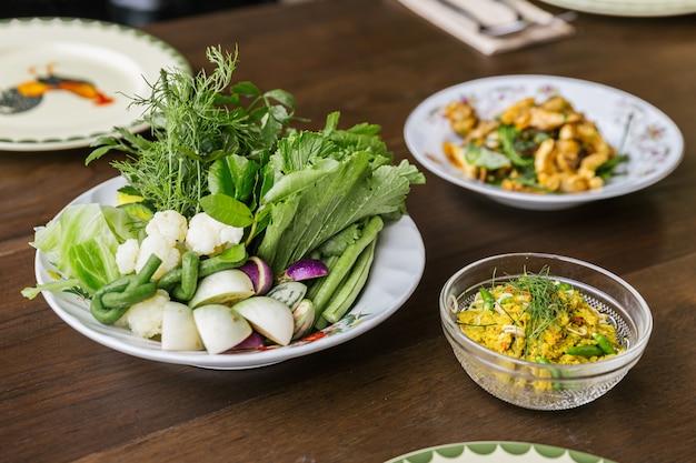 Mescolare la carne di maiale macinata piccante fritta con erbe servite con verdure. cucina tailandese classica.
