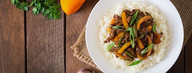 Mescolare la carne fritta con peperoni, fagiolini e riso