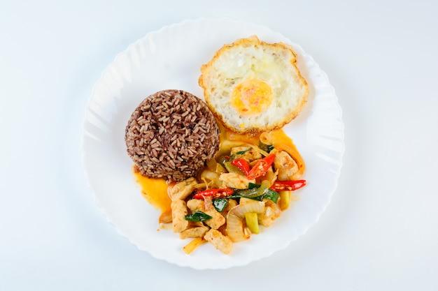 Mescolare la cipolla dolce e i peperoni del pollo fritto, serviti con riso sbramato e l'uovo fritto sul piatto bianco