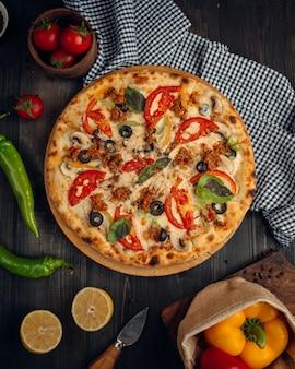 Mescolare la pizza con fette di pomodoro, funghi, olive