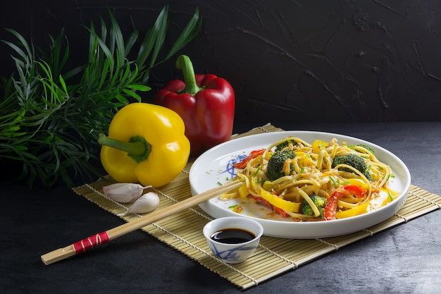 Mescolare tagliatelle fritte con verdure su un piatto bianco con salsa di soia e ingredienti su una stuoia di bambù
