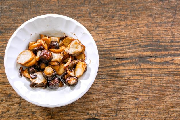 Mescoli freschi del fungo di shiitake fritti con salsa di soia nello stile cinese sul piatto ceramico bianco e su di legno. un cibo vegetariano nel festival vegetariano cinese.