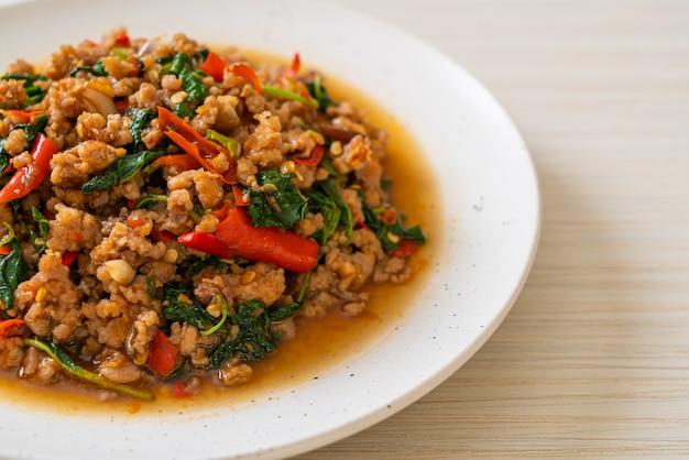 Mescoli il basilico tailandese fritto con carne di maiale e peperoncini rossi tritati, stile tailandese dell'alimento locale