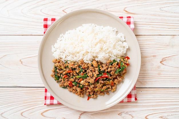 Mescoli il basilico tailandese fritto con carne di maiale tritata e peperoncini rossi su riso sormontato, stile locale dell'alimento tailandese
