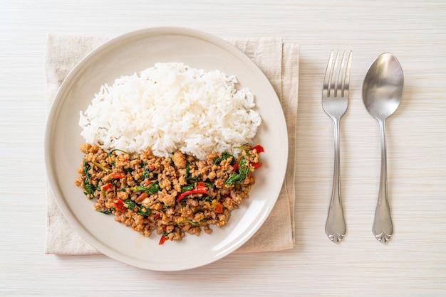Mescoli il basilico tailandese fritto con carne di maiale tritata su riso sormontato
