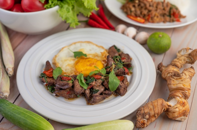 Mescoli il fegato di basilico fritto con l'uovo fritto in un piatto bianco.