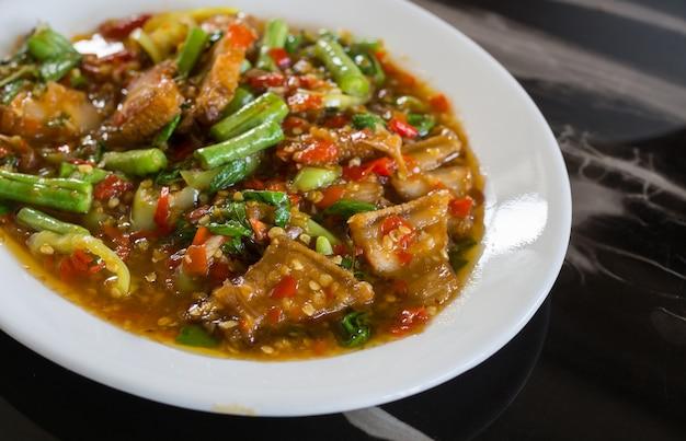 Mescoli la carne di maiale e il basilico fritti sul fondo della tavola, alimento tailandese