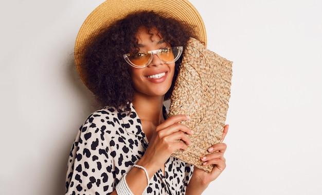 Mescoli la ragazza della corsa in camicetta e cappello di paglia d'avanguardia che controllano la parete bianca. sorriso bianco perfetto. umore dello shopping.