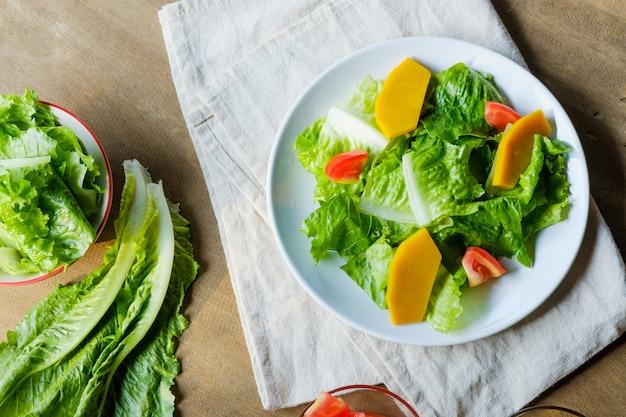 Mescoli la verdura di insalata in piatto bianco, vegano