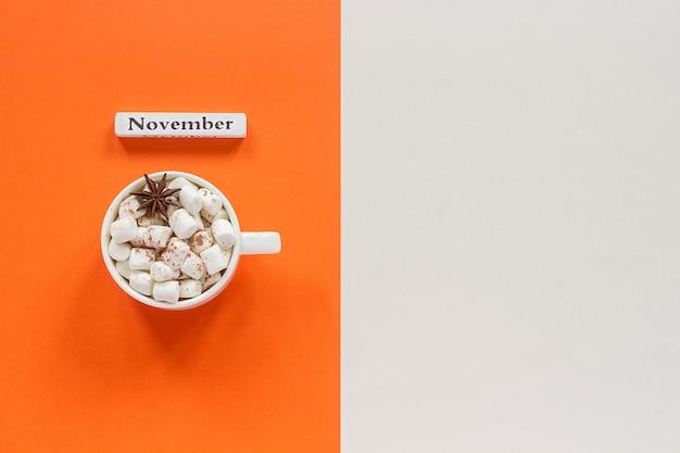 Mese di calendario in legno novembre e tazza di cacao con caramelle gommosa e molle su fondo beige arancio.