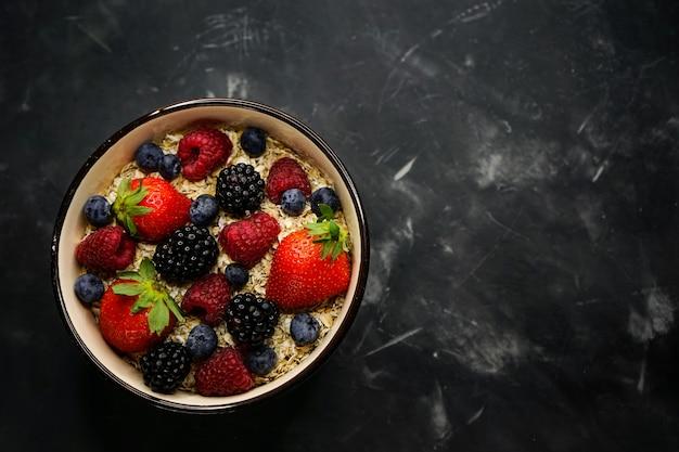 Messa a fuoco selettiva, corretta alimentazione, colazione sana, piastra profonda con cereali, farina d'avena, fragole fresche, lamponi, mirtilli e more