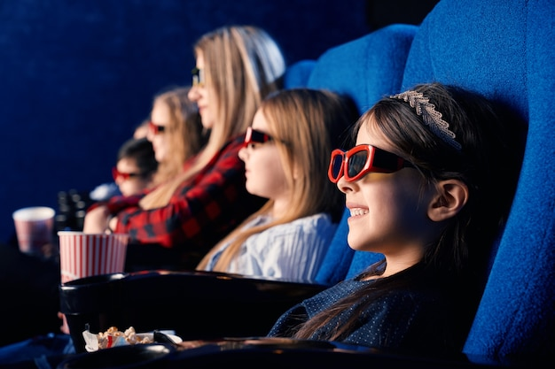Messa a fuoco selettiva del bambino che ride con gli occhiali 3d, mangiare popcorn e guardare film divertenti. bambina sveglia che gode del tempo con gli amici nel cinema