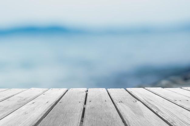 Messa a fuoco selettiva del vecchio tavolo in legno con sfondo bellissimo spiaggia per visualizzare il tuo prodotto.