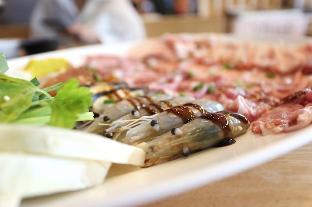 Messa a fuoco selettiva di gamberi freschi con verdure per cucinare o shabu shabu e sukiyaki, cibo giapponese