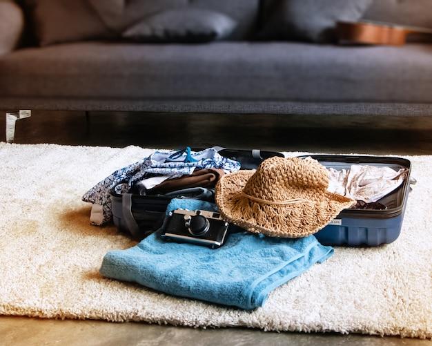 Messa a fuoco selettiva di panni, telo da bagno, cappello e fotocamera. gli accessori per il viaggio di vacanza, messi al piano terra, accanto per il confezionamento, luce sfocata intorno