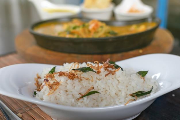 Messa a fuoco selettiva di riso con gamberi al curry in una padella sullo sfondo