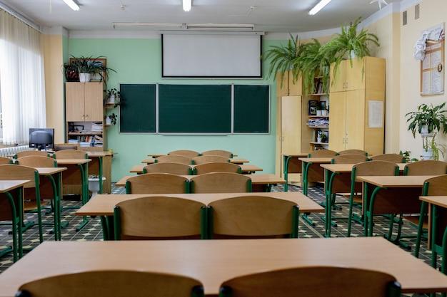 Messa a fuoco selettiva e sfocatura concentrata. vecchie sedie di lezione di fila di legno in aula nella scuola povera. sala studio senza student.concept per l'istruzione