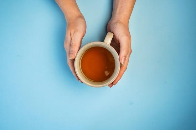 Messa a fuoco selettiva, mani femminili in possesso di una tazza di tè