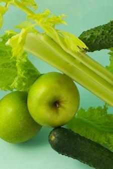 Messa a fuoco selettiva, nutrizione detox, dieta verde su frutta e verdura. prodotti naturali su sfondo blu