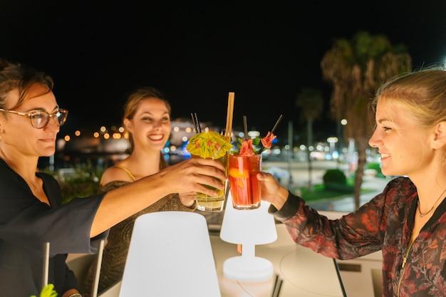 Messa a fuoco selettiva su tre giovani donne fare un brindisi con cocktail su una terrazza di notte