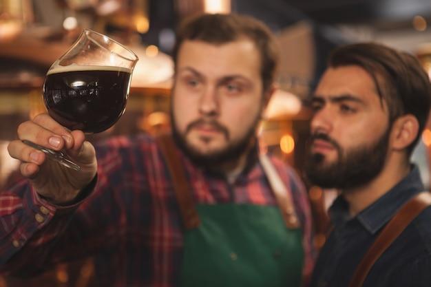 Messa a fuoco selettiva su un bicchiere di birra scura deliziosa nelle mani di birrai professionisti