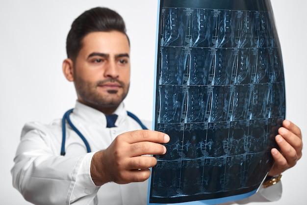 Messa a fuoco selettiva su una risonanza magnetica nelle mani di un maschio bello dottore professione occupazione lavoro carriera lavoro lavoratore lavoro medicina clinica ospedale trattamento radiologia concetto.
