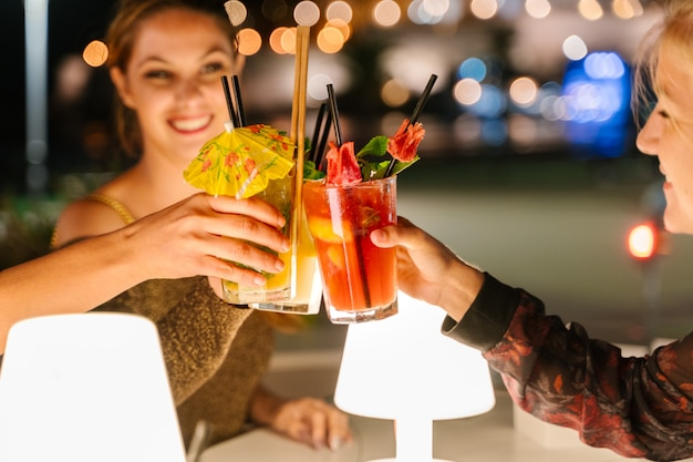 Messa a fuoco selettiva sui bicchieri di tre giovani donne facendo un brindisi con cocktail su una terrazza di notte