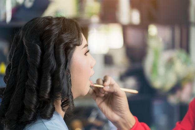 Messa a fuoco selettiva truccatore applicando cipria ad un cliente in un salone di bellezza, dipingendo le labbra della giovane modella ragazza di bellezza. trucco in corso