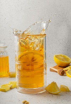 Messa a fuoco selettiva, un bicchiere alto di tè freddo al limone con un vasetto di miele su uno sfondo chiaro