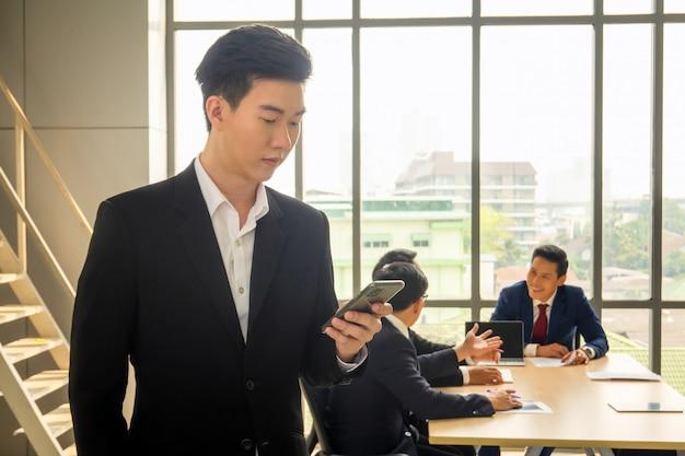 Messa a fuoco selezionata sull'uomo d'affari utilizzando il telefono cellulare contro un gruppo di uomini d'affari riuniti in ufficio