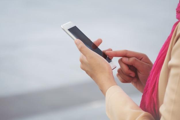Messaggio arabo della donna di affari su un telefono cellulare nella città
